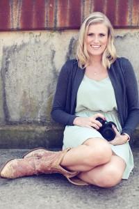 Hochzeitsfotografin Fulda Paulette Wise lacht fröhlich mit Kamera in der Hand und Cowboystiefeln.