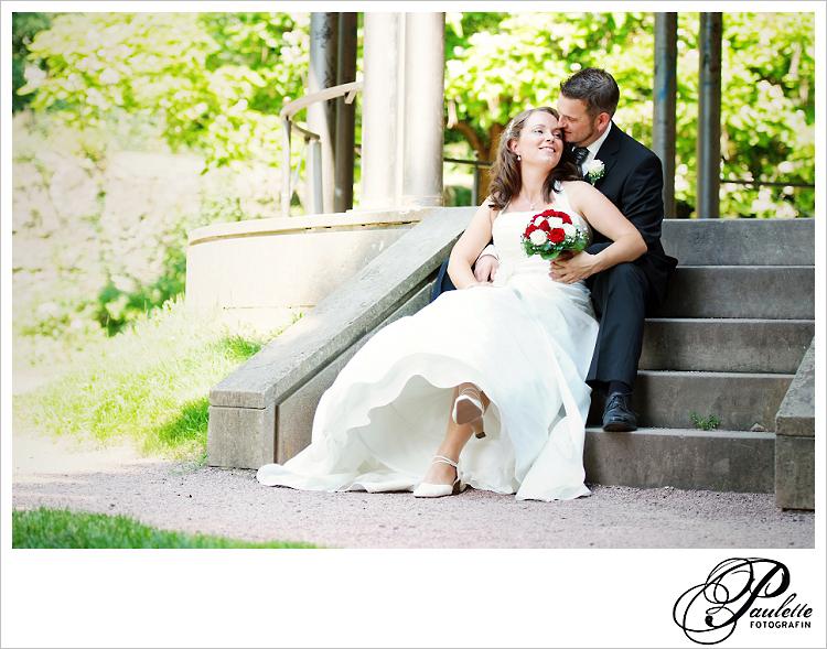 Romantisches lachendes Brautpaar sitzt auf einer Treppe unter einem Pavillon im Schlossgarten Fulda, der Bräutigam küsst seine Braut auf die Stirn.