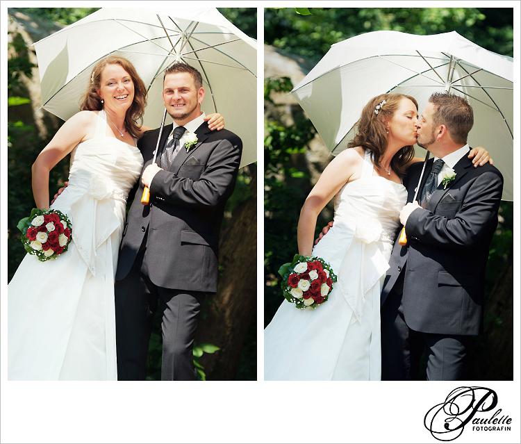 Lächelndes Hochzeitspaar mit Sonnenschirm lacht in Paulette Fotografins Kamera im Schlossgarten Fulda.