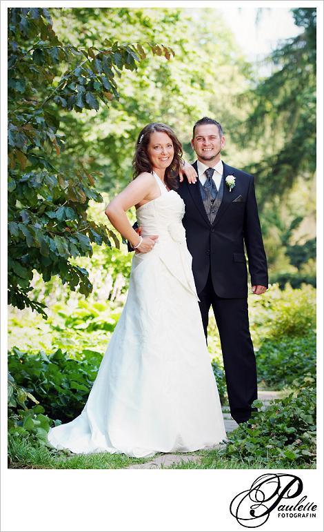 Fröhliche Braut und Bräutigam lassen sich im Schlossgarten Fulda an ihrem Hochzeitstag fotografieren.