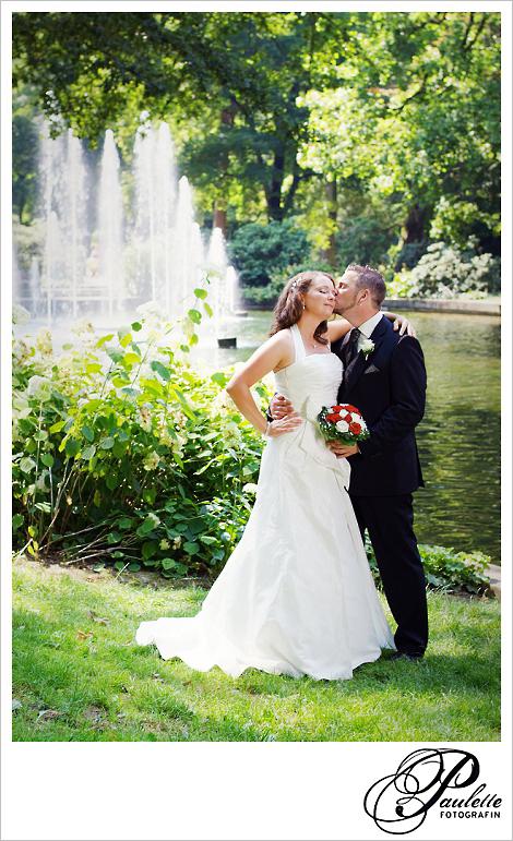 Bräutigam küsste seine Braut zärtlich auf die Wange beim Hochzeitsportraitshooting vor den Fontänen im Schlossgarten Fulda.