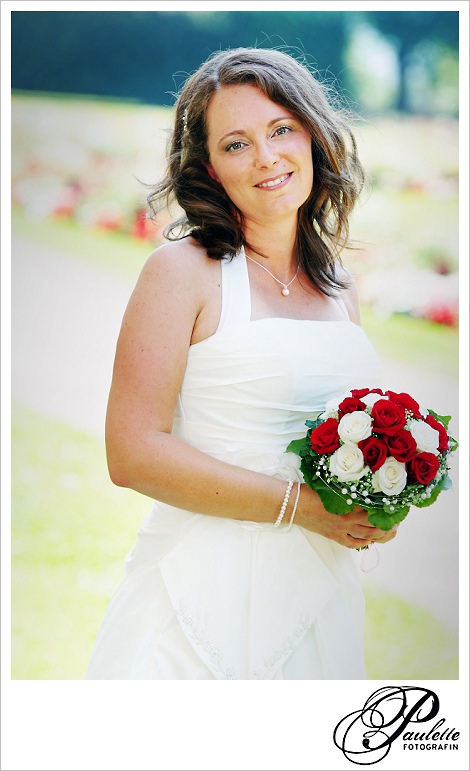 Strahlende Braut mit Braustrauss aus roten und weissen Rosen im Schlossgarten Fulda.
