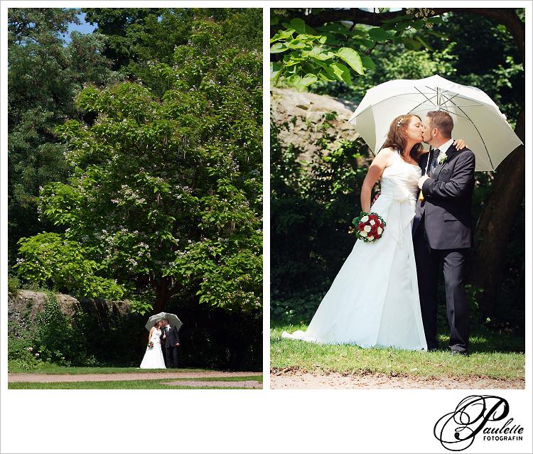 Brautpaar küsst sich unter einem großen Braum mit Sonnenschirm im Schlossgarten Fulda.