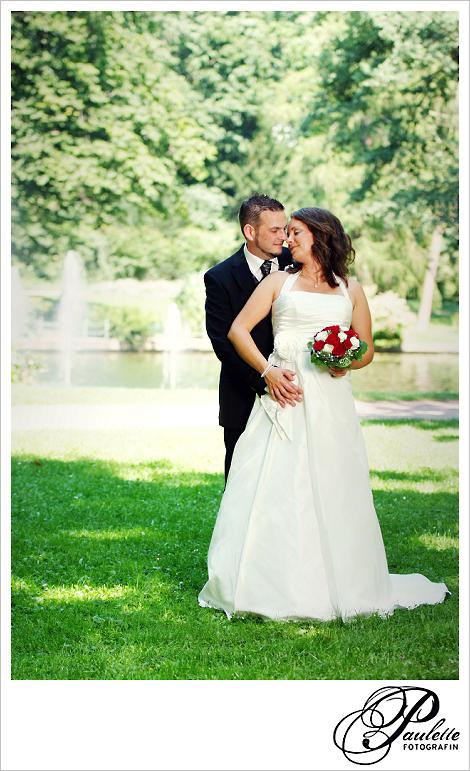 Hochzeitspaar fotografiert vor dem Springbrunnen im Schlossgarten Fulda, Braut hält einen Brautstrauss mit roten und weissen Rosen.