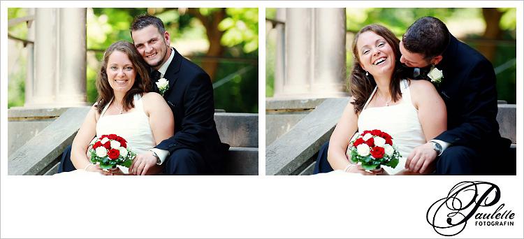 Brautpaar lacht an ihrem Hochzeitstag und sitzt auf der Treppe beim Pavillon im Schlossgarten Fulda.