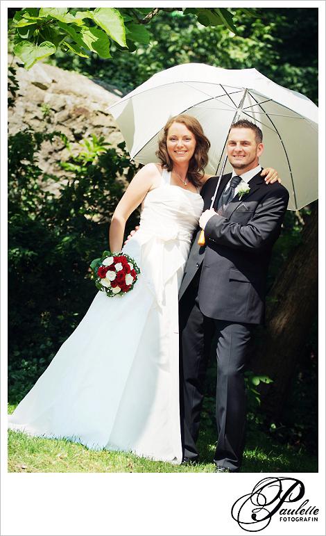 Lachendes Brautpaar steht mit einem weissen Sonnenschirm unter einem Baum im Schlossgarten Fulda.
