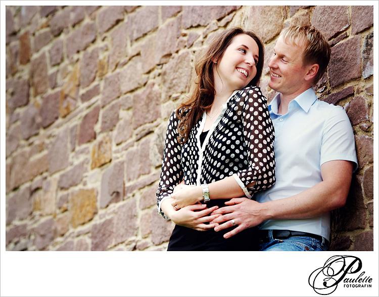 Verliebtes Paar lehnt an einer Sandstein Mauer in der Propstei Johannesberg Fulda  beim Engagement Portrait Paar Fotoshooting für die Hochzeitseinladung.