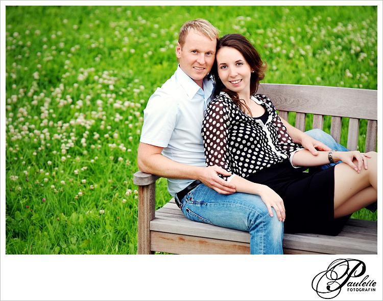 Verliebtes Paar sitzt auf einer Bank in einer wild Blumenwiese in der Propstei Johannesberg in Fulda beim Engagement Portrait Paar Fotoshooting für die Hochzeitseinladungskarte.