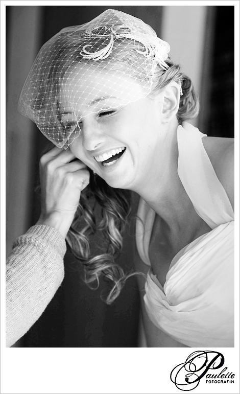 Lachende, fröhliche Braut mit kurzem weissen Netzschleier beim Getting ready.