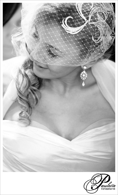 Klassisch schöne Braut im 20er Jahre Look mit kurzem weissen Netzschleier beim Getting ready.