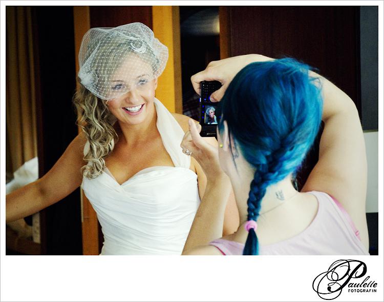 Strahlende Braut mit kurzem weissen Netzschleier wird mit dem Handy von einem Mädchen mit blauen Haaren fotografiert.