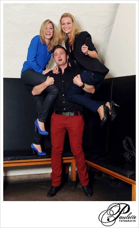 Starkes Geburtstagskind hebt zwei hüpsche Maedels auf den arm im Photobooth zur 30. Geburtstagsfeier Party im Museumskeller Fulda, rote Hose.