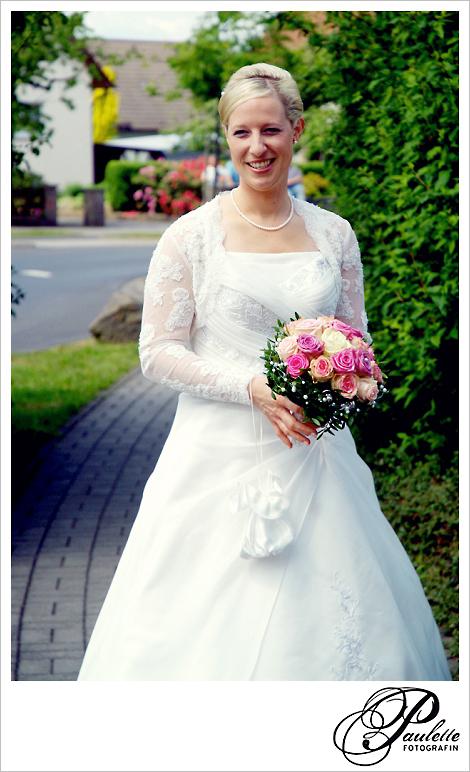 Glückliche Braut mit rosa Rosen Brautstrauss und Spitzen Bolero kurz vor ihrer kirchlichen Trauung in Fulda Bronnzell.