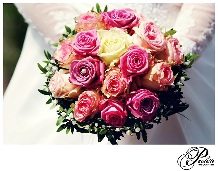 Klassischer Brautstrauss mit rosa, lila und creme farbenen Rosen mit Perlen gehalten von der Braut mit Spitzen Ärmeln.