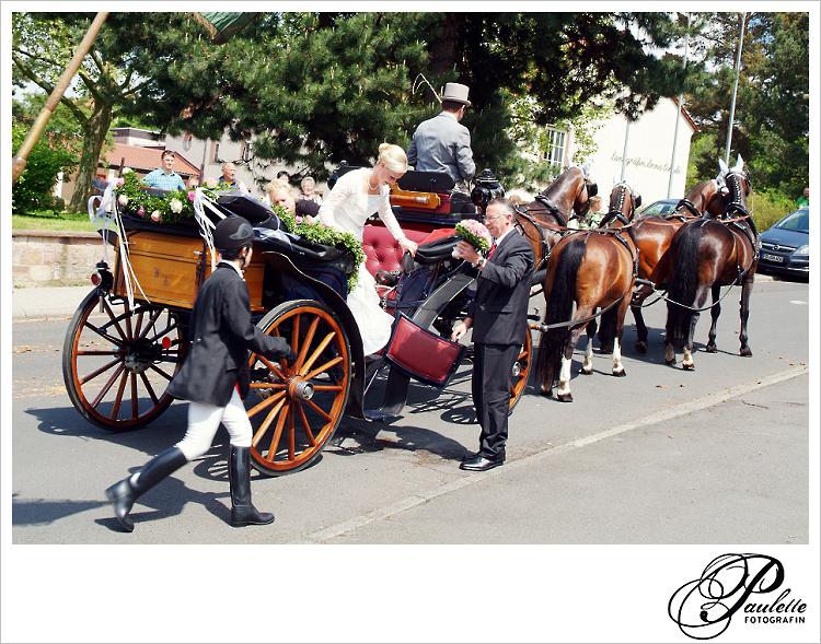 Vater der Braut hilft seiner Tochter von der Hochzeitskutsche vor ihrer kirchlichen Trauung in Fulda Bronnzell.