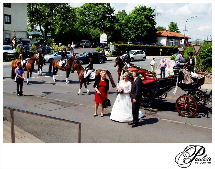 Mutter und Vater der Braut vor der Hochzeitskutsche mit Reitergefolge und Pferden vor der Kirche in Fulda Bronnzell.