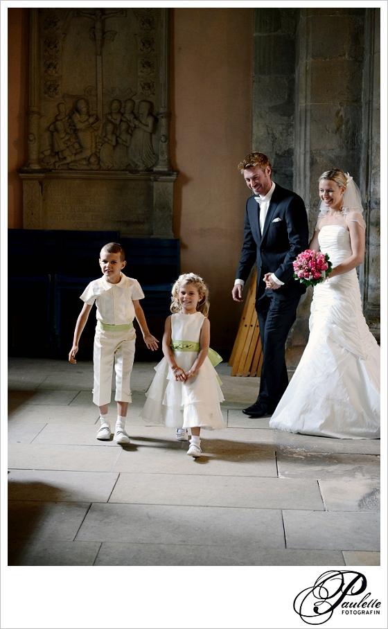 Blondes Brautpaar schreitet in die Kirche mit zwei Blumenkindern bei ihrer Hochzeit in Hannover.