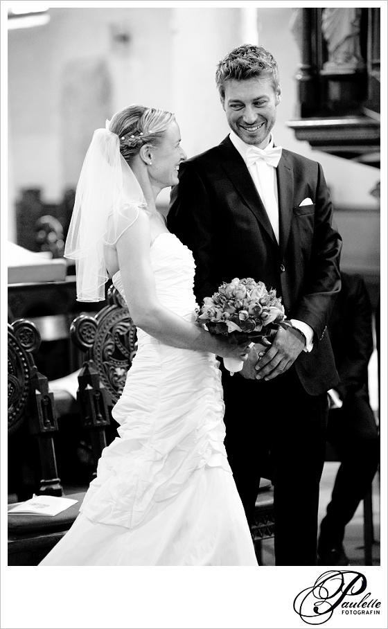 Hübsches Brautpaar lächelt sich an am Altar beim Ja-Wort in der Kirche in Hannover.