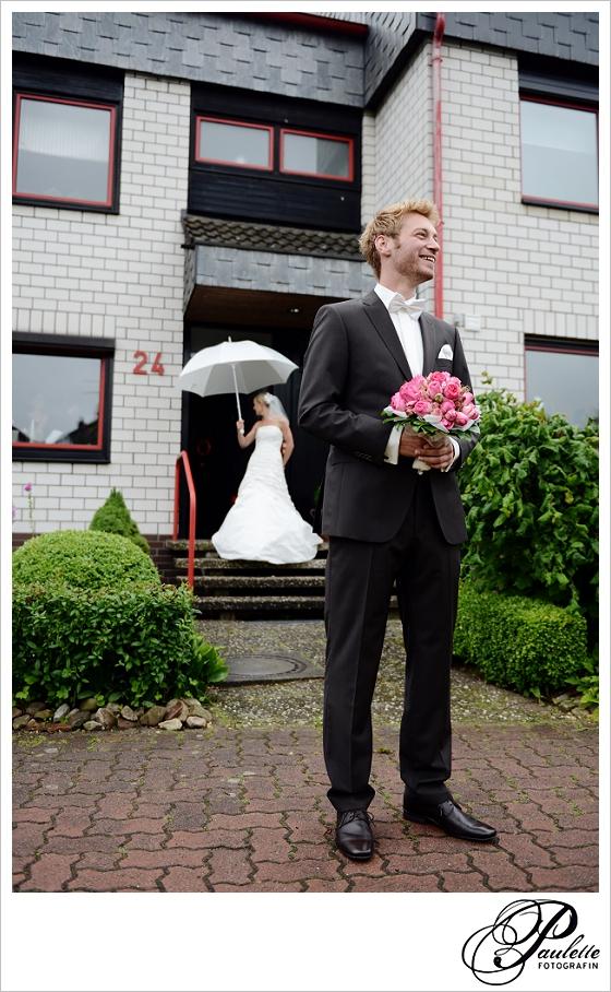 Blonder Bräutigam steht vor Haus mit Brautstrauss und wartet auf seine braut mit Regenschirm beim First Look in Wunstorf bei Hannover.