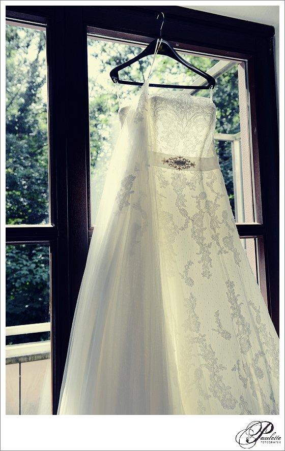 Romantisches Hochzeitskleid mit Spitze und Brosche trägerlos hängt beim getting ready im Fenster im Hotel Maritim am Schlossgarten in Fulda