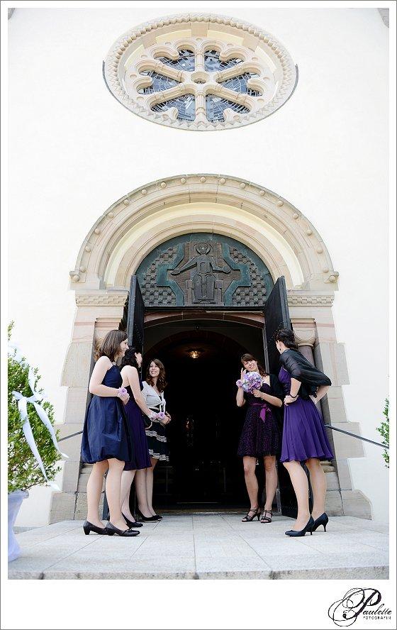Brautjungfern mit Lila Kleidern warten vor der Kirche auf die Braut bei der Trauung in Eisenach.