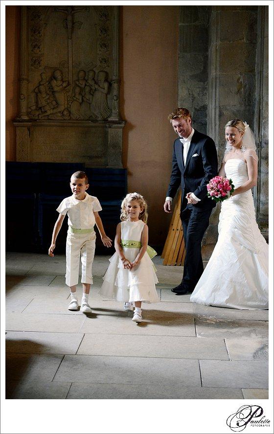 Strahlendes Brautpaar läuft in die Kirche mit Brautmädchen und Brautjungen zur Hochzeit in Hannover.