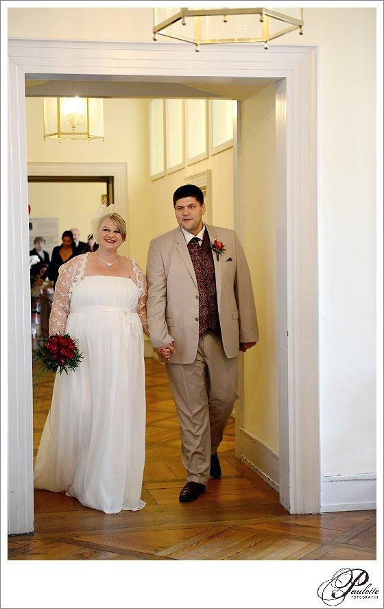 Schwangeres Brautpaar läuft lächelnd ins Standesamt in Fulda zur standesamtlichen Trauung.