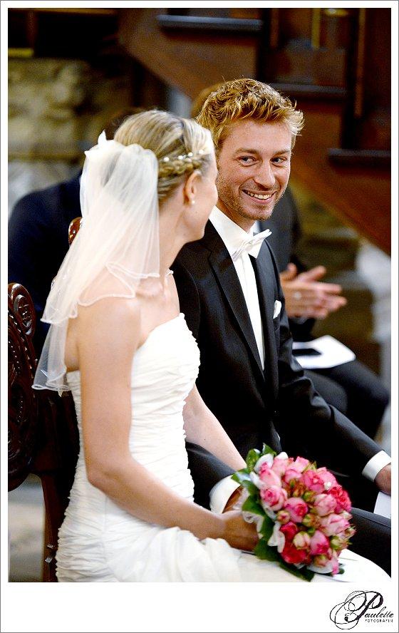 Blonder Bräutigam strahlt seine Brau an in der Kirche bei der kirchlichen Trauung.