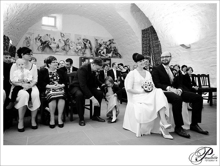 Brautpaar und Hochzeitsgäste lachen bei der standesamtlichen Trauung im Gewölbekeller im Schloss Gerisa.