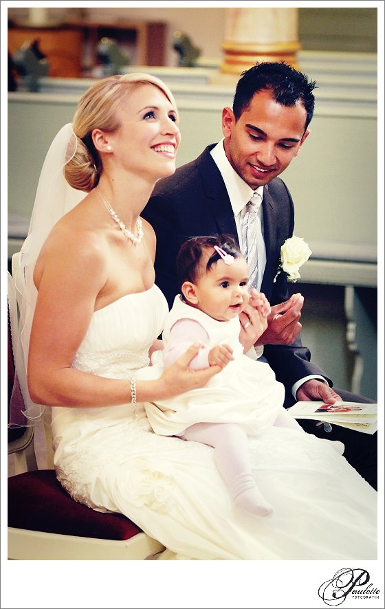 Blonde Braut und dunkelhäutiger Bräutigam lachen in der Kirche bei der kirchlichen Trauung und Taufe ihrer kleinen Tochter.