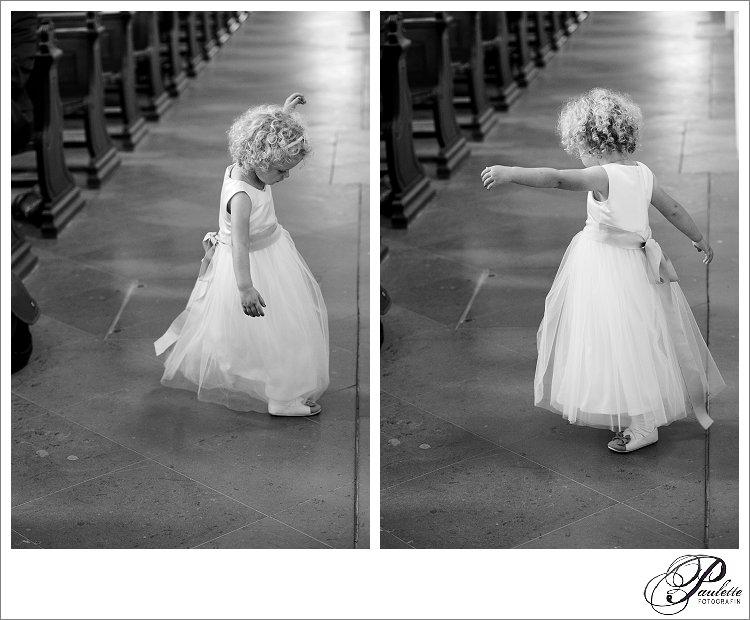 Kleine Brautjungfer tanzt in der Kirche und dreht sich mit ihren kleinen blonden Locken im Kirchengang.