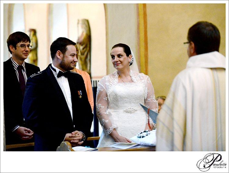 Braut mit Hochzeitskleid aus Spitze strahlt ihren Bräutigam in Uniform and bei der kirchlichen Trauung in der Michaelskirche in Fulda.