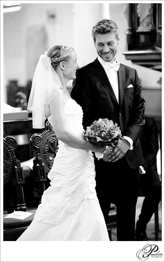 Blonder Bräutigam strahlt seine blonde Braut an bei der kirchlichen Trauung in Hannover vor dem Eheversprechen.