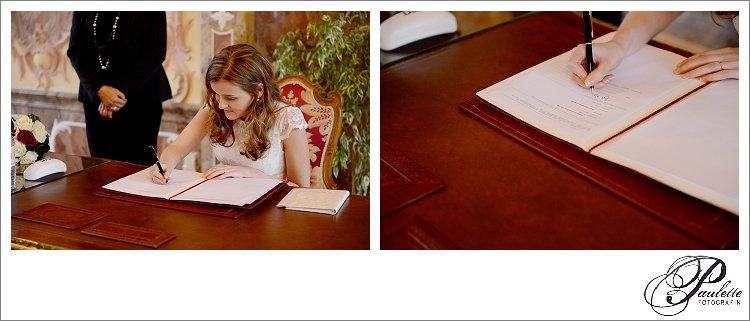 Eine Braut unterschreibt mit ihrem neuen Ehenamen bei der standesamtlichen Trauung im Rokokosaal im Stadtschloss in Fulda.