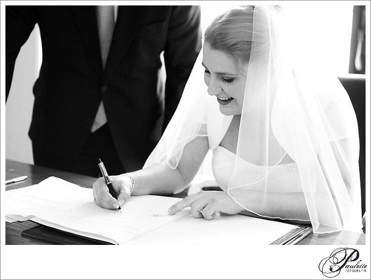 Eine Braut mit Schleier unterschriebt mit ihrem neuen Ehenamen bei der standesamtlichen Taruung im Stadtschloss Fulda.
