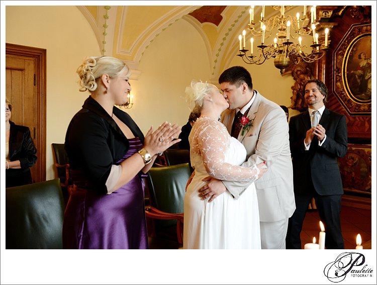 Die Trauzeugen und Hochzeitsgäste applaudieren beim ersten Kuss als Mann und Frau bei der standesamtlichen Trauung in der Schlosskapelle in Fulda.