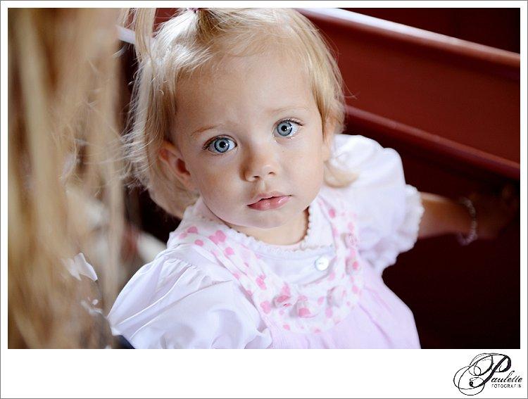 Ein kleines Mädchen mit strahlend blauen Augen schaut die Hochzeitsfotografin Paulette direkt in der Kirche.
