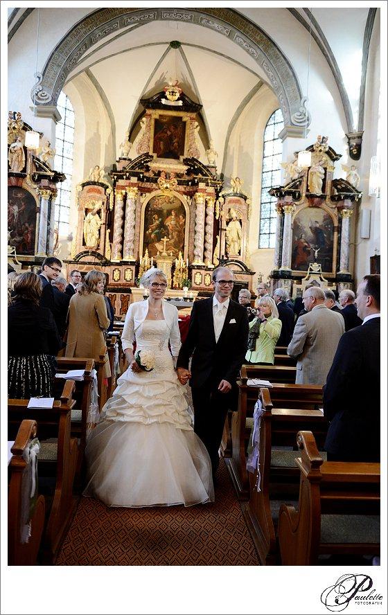 Braut mit Brille und Bräutigam mit Brille laufen aus der Kirche beim Auszug in Johannesberg bei Fulda.