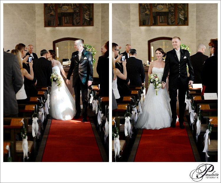 Die Braut küsst ihren Vater auf die Wange beim Auszug mit dem Bräutigam aus der Kirche.