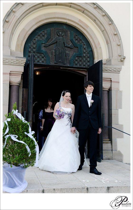 Junges Brautpaar mit lila Kleid läuft aus der Kirche in Eisennach nach der kirchlichen Trauung.