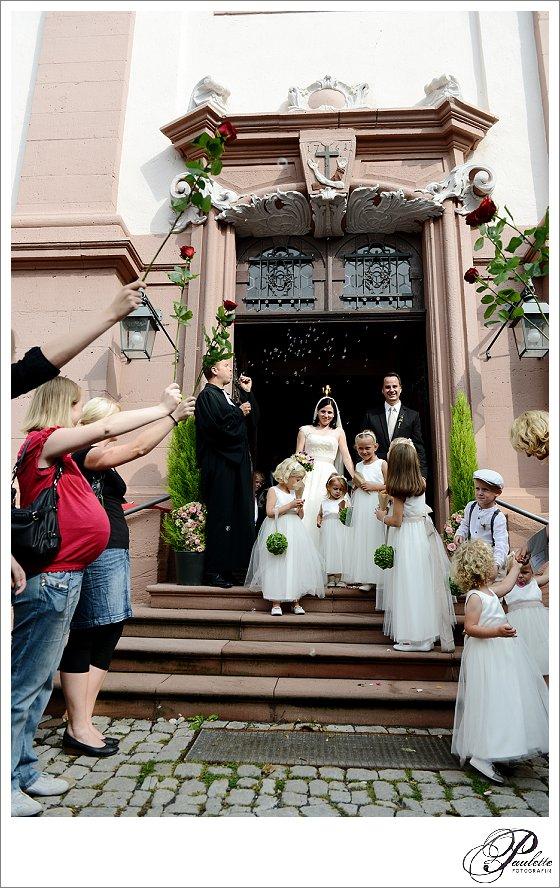 Der Pfarrer bläst Seifenblasen und die Gäste halten Rosen im Spalier als das Brautpaar mit Brautkindern aus der Kirche am Frauenberg in Fulda läuft.