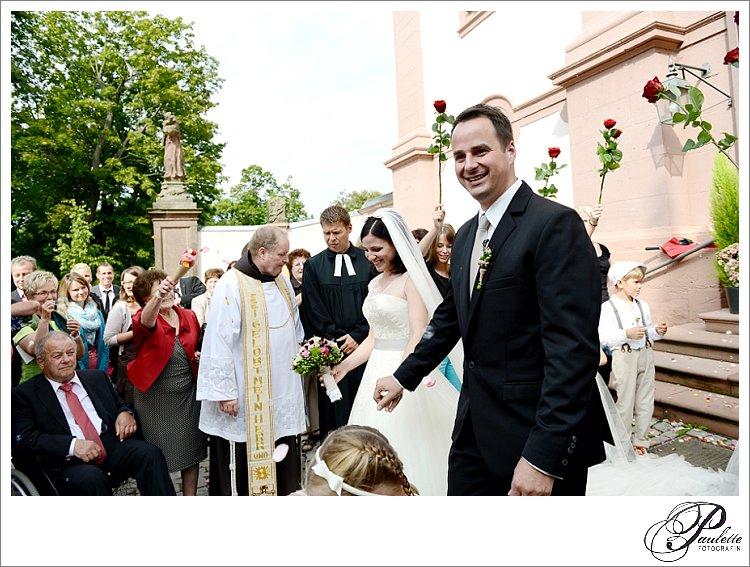 Strahlendes Brautpaar läuft aus der Kirche am Frauenberg in Fulda durch ihre Gäste die Rosenblätter werfen.