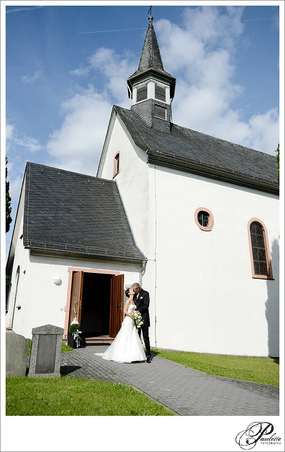 Brautpaar küsst sich vor der kleinen Kapelle in Frankfurt am Main nach der kirchlichen Hochzeit.