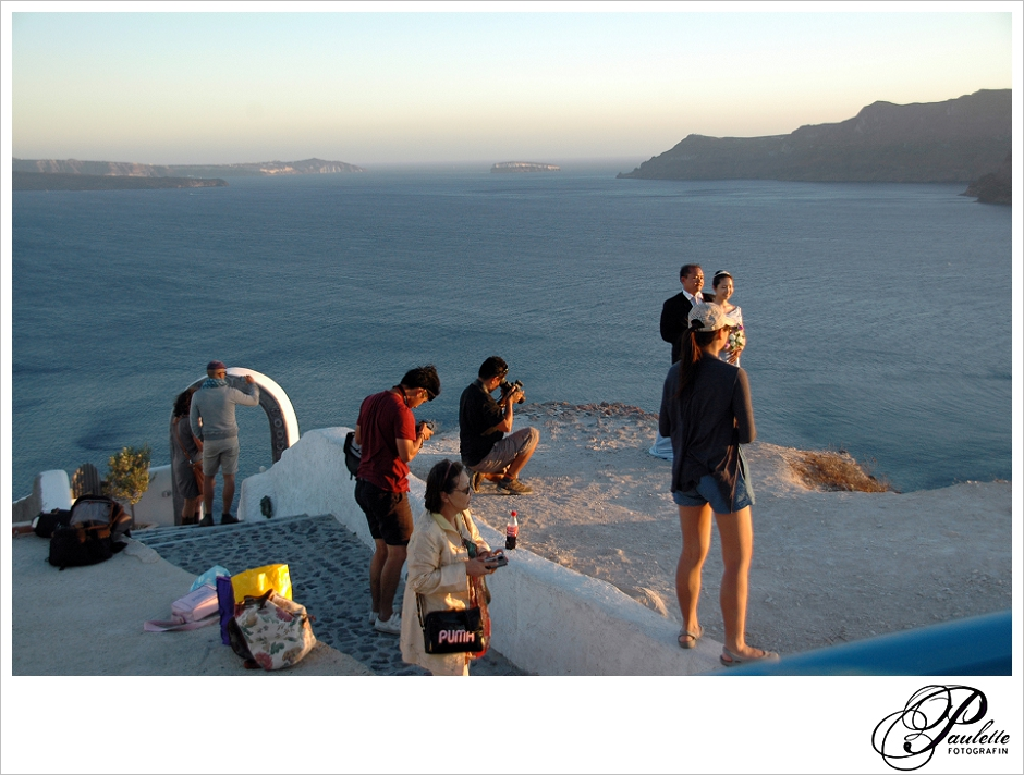 Asian wedding couple takes after wedding photo on the Greek Island of Santorini in the Cyclades.