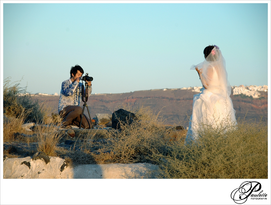Husband takes after wedding photos of his bride on the Greek Island of Santorini during sunset in the Cyclades.